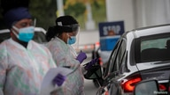 Medical technicians work at a drive-thru coronavirus disease (COVID-19) testing facility at the Regeneron Pharmaceuticals…