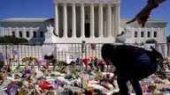A woman places flowers as people mourn the death of Associate Justice Ruth Bader Ginsburg at the Supreme Court.