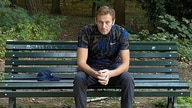Russian opposition politician Alexei Navalny sits on a bench while posing for a picture in Berlin, Germany.