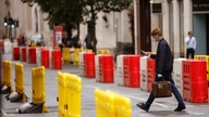 A man wearing a face mask crosses a road laid out with social distancing barriers in the City of London financial district amid…