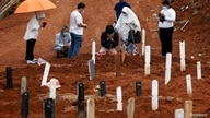 Relatives mourn during the funeral of their family member at the burial area provided by the government for victims of the…