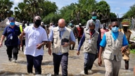 Alain Noudehou, UN Humanitarian Coordinator in South Sudan, and Matthew HollingWorth, the Country Director of World Food Program (WFP), wade through flood water in Duk padiet county of Jonglei State, in South Sudan, Sept. 24, 2020.