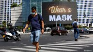 People walk near a billboard as Israel imposes a second nationwide coronavirus disease (COVID-19) lockdown amid a rise in…