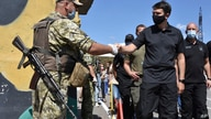 Ukraine's parliament speaker Dmytro Razumkov, right, greets a soldier at a checkpoint in Mayorsk, Donetsk region, Ukraine,…