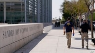FILE - Federal law enforcement personnel walk past the Sandra Day O'Connor Federal Courthouse, Sept. 15, 2020, in Phoenix.