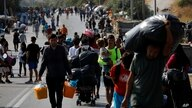 Migrants carry their belongings as they flee a road leading from Moria to the capital of Mytilene, on the northeastern island…