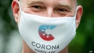 Rainer Knirsch, Telekom press spokesman, wears a mouth and nose protector with the app's logo at the beginning of a press conference on the 100-day Corona Warning App at the Federal Press Conference Center in Berlin, Sept. 23, 2020.