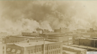 Black Wall Street burns in Tulsa, Oklahoma, June 1921. (Courtesy Greenwood Cultural Center)