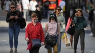 FILE - Shoppers, some wearing masks, walk on Oxford Street in London, Britain, Sept. 21, 2020.