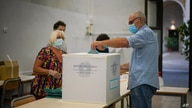 A man casts his ballot at a polling station, in Rome, Sept. 20, 2020.