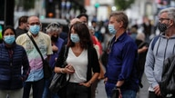 People wearing face masks to protect against the coronavirus queue to buy lottery tickets in downtown Madrid, Spain, Sept. 18, 2020.
