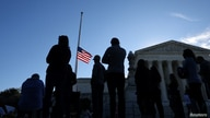 A U.S. flag is seen at half mast as people gather in front of the U.S. Supreme Court following the death of U.S. Supreme Court Justice Ruth Bader Ginsburg, in Washington, Sept. 19, 2020.