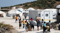 Refugees and migrants from the destroyed Moria camp enter a new temporary camp on the island of Lesbos, Greece, Sept. 20, 2020.