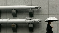 A man holding an umbrella walks past a torpedo on display outside the Taiwan Armed Forces Museum in Taipei January 7, 2010. The…