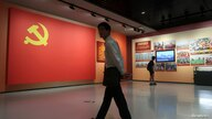 A man walks past a section featuring a flag of Chinese Communist Party next to its loyalty oath at an exhibition marking the…