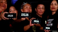 "Journalists, including Rappler CEO Maria Ressa, raise their smart phones with words ""STOP THE ATTACKS!"" in a rally for press…"