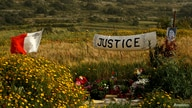FILE PHOTO: A banner calling for justice is seen next to a photo of assassinated anti-corruption journalist Daphne Caruana…