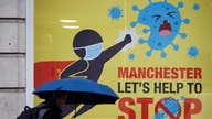 A man walks past a poster amid the outbreak of the coronavirus disease (COVID-19), in Manchester, Britain October 21, 2020…