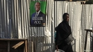 A woman walks past a campaign poster of a presidential candidate Alassane Ouattara of the ruling RHDP coalition, in Attecoube district, Abidjan, Ivory Coast, Oct. 23, 2020.