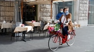 A woman wearing a protective face mask rides a bicycle past a restaurant as the outbreak of the coronavirus disease (COVID-19)…
