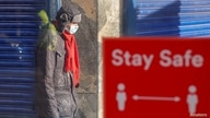 FILE PHOTO: A person wearing a protective mask walks near a social distancing sign, amid the outbreak of the coronavirus…