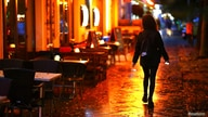 FILE PHOTO: A woman passes empty tables before the late-night curfew due to restrictions against the spread of the coronavirus…