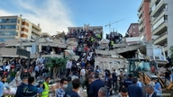 Locals and officials search for survivors at a collapsed building after a strong earthquake struck the Aegean Sea on Friday and…