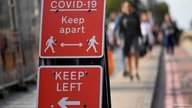 FILE PHOTO: Pedestrians walk near public health signs in London, Britain, September 11, 2020. REUTERS/Toby Melville/File Photo