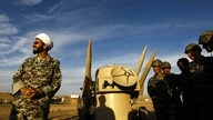 FILE - In this Nov. 13, 2012 file photo, an Iranian clergyman stands next to missiles and army troops, during a manoeuvre, in…