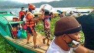 In this photo provided by the Philippine Coast Guard, families are evacuated to safer ground in Camarines Sur province, eastern…