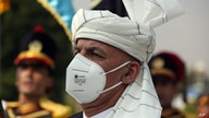 FILE - Afghan President Ashraf Ghani, wearing a mask to help curb the spread of the coronavirus, sings the national anthem at the Independence Minaret monument during the Independence Day celebrations in Kabul, Afghanistan, Aug. 18, 2020.