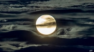 FILE - In this Sept. 2, 2020 file photo, the full moon shines surrounded by clouds in the outskirts of Frankfurt, Germany. …