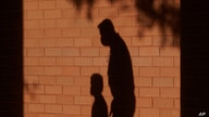 The shadow of a school employee escorting a student is cast on the wall as they walk to a classroom on the first day of class…