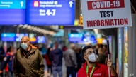A man holds a sign leading the way to a Covid-19 test center the airport in Frankfurt, Germany, Oct. 22, 2020.