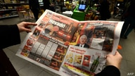 "A woman reads the ""Blesk"" Czech tabloid newspaper with images of the of the Czech Republic's Minister of Health Roman Prymula allegedly dining at a restaurant despite recent coronavirus restrictions, in Prague, Oct. 23, 2020."