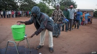 FILE - People queue to wash their hands to protect against the coronavirus before lining up to vote at a polling station, in Lilongwe, Malawi, June 23, 2020. The COVID pandemic has led to a spike in suicides in the southeastern African country.