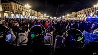 Police face people protesting new government restrictions to curb the spread of the coronavirus, in Turin, Italy, Oct. 26, 2020.