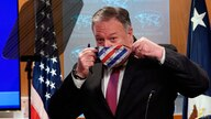 U.S. Secretary of State Mike Pompeo puts on a face mask after speaking at a news conference at the State Department in Washington, Oct. 21, 2020.