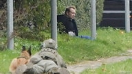 A man resembling Peter Madsen sits up against a fence surrounded by police forces in Albertslund, Denmark, Oct. 20, 2020.