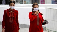 Turkmen women wearing face masks walk in Ashgabat on July 13, 2020. - Reclusive Turkmenistan on July 13 recommended that…