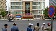 Security personnel stand across the street in front of Phnom Penh Municipal Court as authorities brought Rong Chhun, the leader…