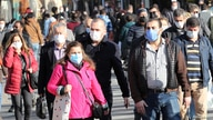 Pedestrians wearing face masks walk in Ankara on November 13, 2020, amid the Covid-19 pandemic, caused by the novel coronavirus…