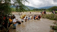Migrants use a rope to cross the Tachira river, the natural border between Colombia and Venezuela, as the official border…