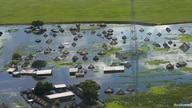 An aerial view shows flooded homes within a village after the River Nile broke the dykes in Jonglei State, South Sudan October…