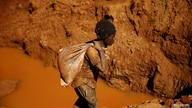Illegal artisanal gold miners work at an open mine in Zimbabwe,  after occupying parts of Smithfield farm, owned by the former President…