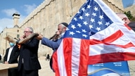 Israeli settlers blow the Shofar, a ceremonial ram's horn, as they gather to show their support for U.S. President Donald Trump.
