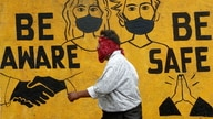 A man walks past a graffiti amid the spread of the coronavirus disease (COVID-19) in Mumbai, India, November 2, 2020. REUTERS…