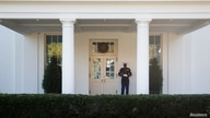 A United States Marine stands guard in front of the west wing of the White House.