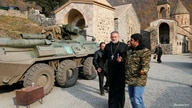 The monastery's abbot Father Hovhannes walks past a military vehicle of the Russian peacekeeping forces at the Dadivank, an…