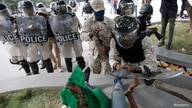 A Haitian National Police (PNH) officer pushes a protestor during clashes at a demonstration in Haiti.